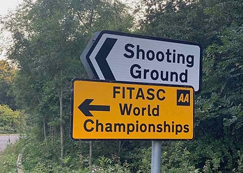 Yellow AA display notice directing to FITASC World Championships & standard white road signs for Shooting Ground direction.