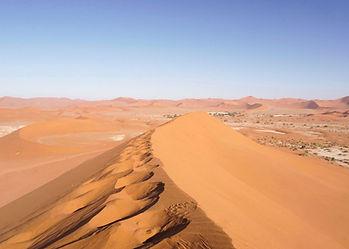 Red dunes of Sossusvlei in the Namib Desert of Namibia, sandy ridgeline running towards distant skyline hills.