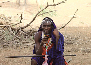 Maasai tribesman on mobile telephone in dry Masailand bush, Tanzania, contact us for East Africa hunting safaris.