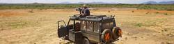 Safari wildlife film photographer on top of land cruiser in dry dusty African bushland of Tanzania.