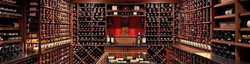 Wine cellar with champagne & sloe gin bottles displayed on all walls in wooden racks.