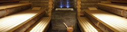 Inside of a spa hotel wood sauna, with grey stone heat stove, part of bespoke client service.
