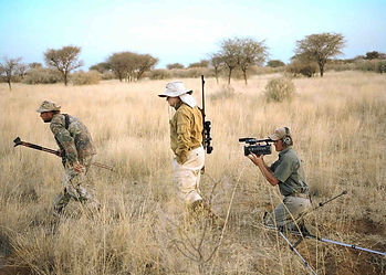 Safari film crew with camera equipment following a professional hunter & guest for plains game in savanna bushland, Tanzania.