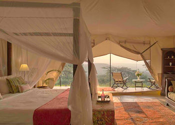 Traditional luxury safari tent bedroom, mosquito net & wooden furniture in view, looking out over Masailand with deck chair.