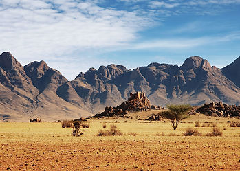 Stoney desert scrub with rocky outcrops in front of Namibia mountain sustainable hunting concession.