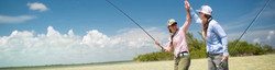 Two fisherwomen high fiving on the sunny sand flat tropical waters of Kenya, with flyfishing rods.