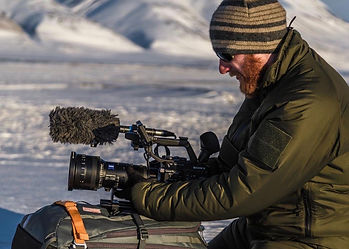 Byron Pace setting up film & videography camera equipment in bare cold snow covered landscape.