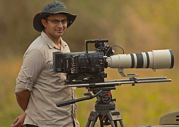 Wildlife safari cameraman with film & videography equipment on tripod, ready for action in the Masailand bush of Africa.