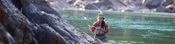 Attractive brunette fisherwoman, flyfishing on calm river next to large rock, with sunglasses.