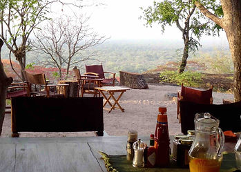 Classic luxury hunting safaris camp, wooden decking & chairs on sandy ground with views over Masai thorn bushland, Tanzania.