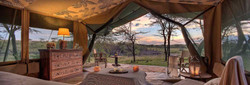 Traditional East African safari camp bedroom tent, looking out to classic thornbush of Tanzania.