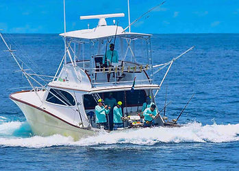 Big game fishing sea safari boat with crew tending rods & lines for marlin, sailfish & tuna, off Kenya coast at Malindi.