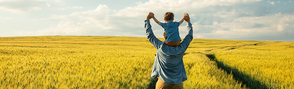 Father carrying son on shoulders in a wheat field