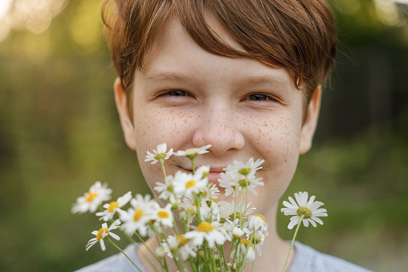 Young boy with freckles smiling and holding daisies