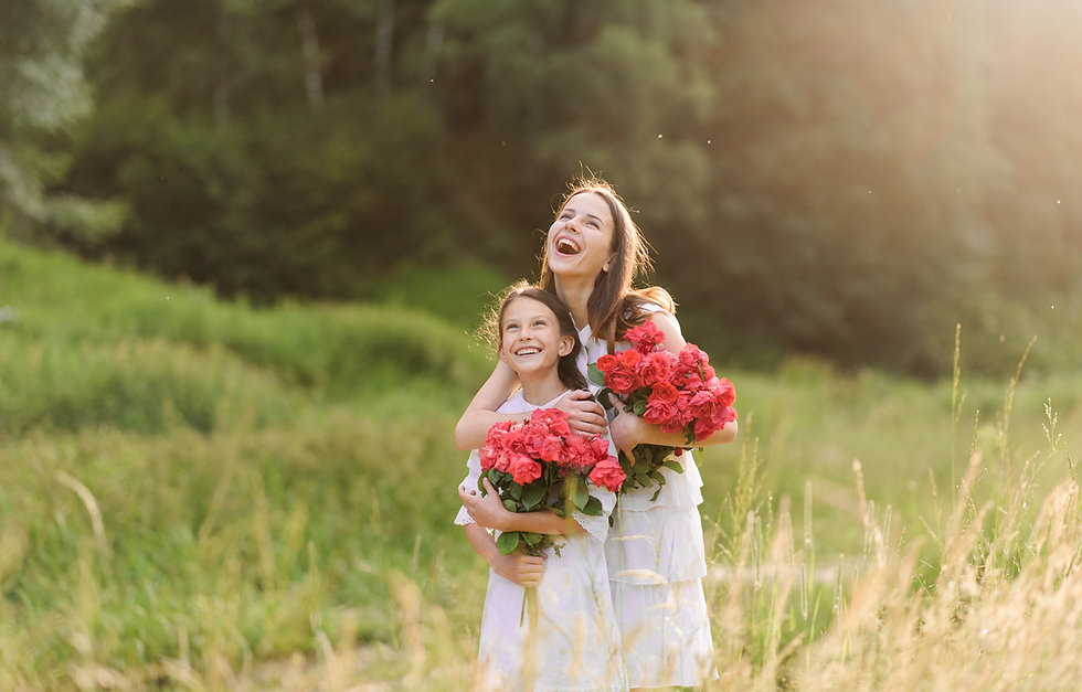 Two young sisters embracing with flowers smiling in a green field