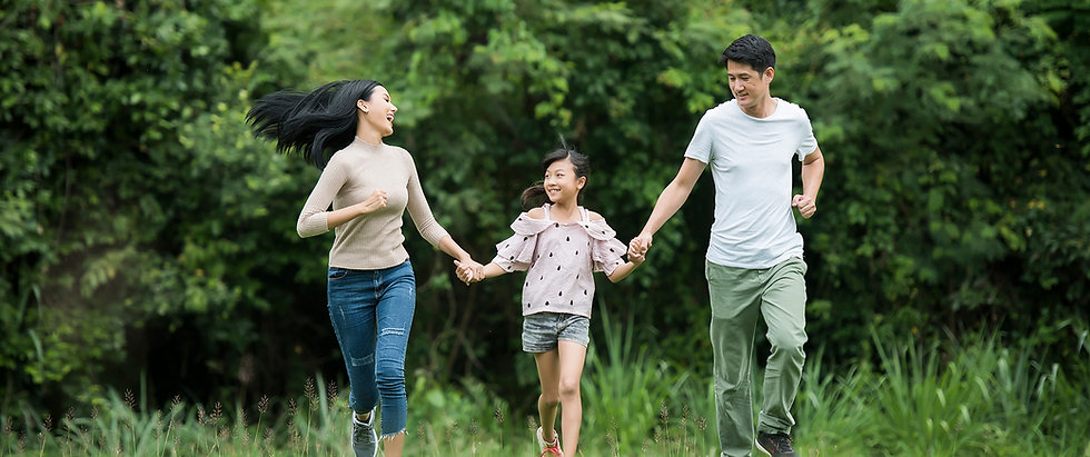 Couple with young daughter holding hands running and smiling in a lush green field