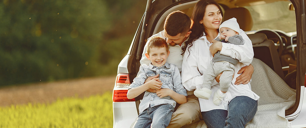 Couple with baby and young boy tailgaiting in a white SUV outdoors in a field