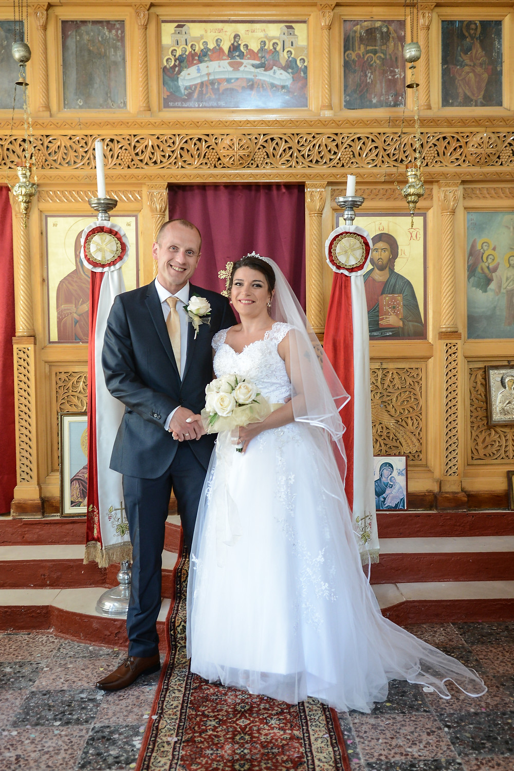 Bride & Groom standing inside the Panagitsa chapel infront of the iconostas in Parga
