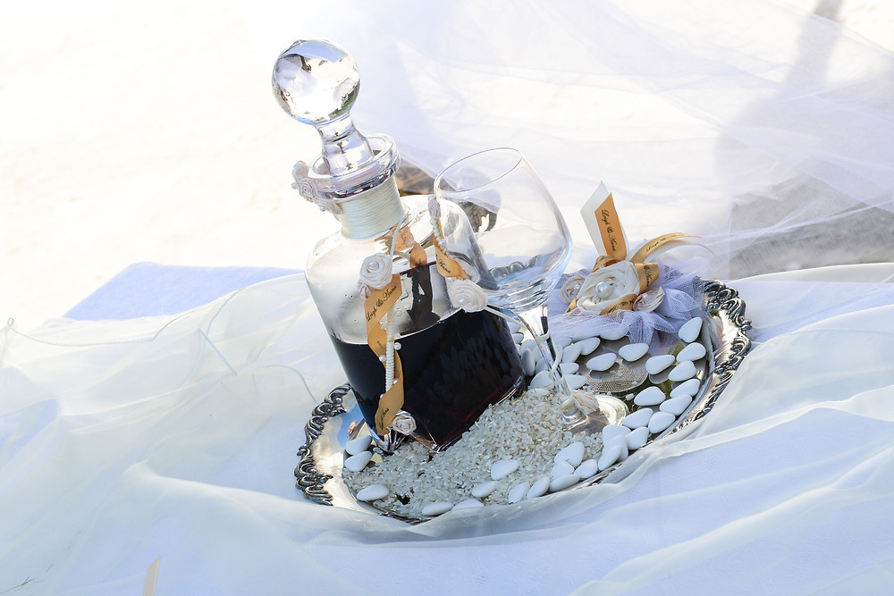 Caraf of sweet red wine and the common cup for the Greek Orthodox wedding placed on a silver trey with sweets and rice