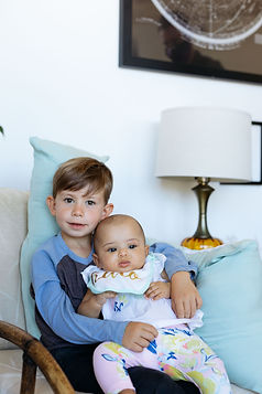Big brother using The Chase pillow for support while holding baby.