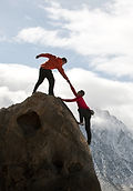 helping someone summit a mountain