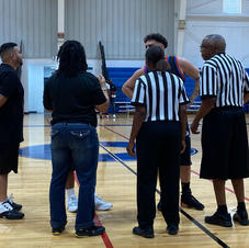 Coach T meeting with the team captains & refs before the tip-off