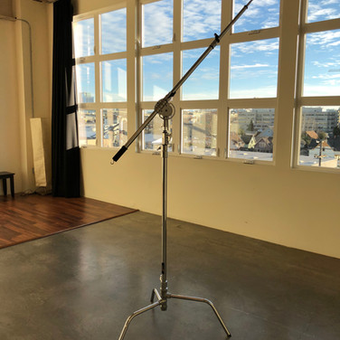 This heavy duty c-stand has an extenable arm for a light or microphone. There are counter weight sand bags to that hang on the hook. The arm can be removed so that the stand becomes a mount for a light. Always, place the long leg forward so that it securely holds the top weight.