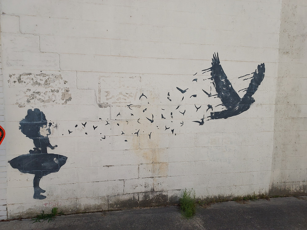 mural on the side of a building in Cary, NC, of a little girl blowing a dandelion, the fluff turning into a large raven as it flies away