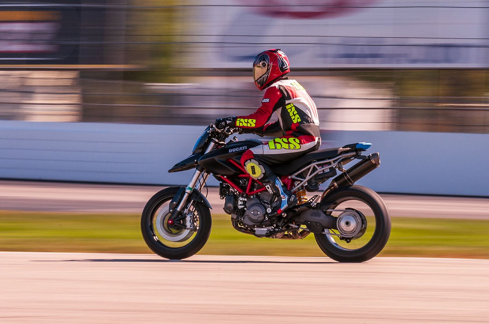 Panning shot of a motorcyclist at a track day.
