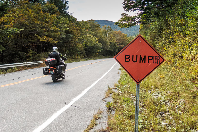 Motorcycle on the App-Gap rides past bumpier sign