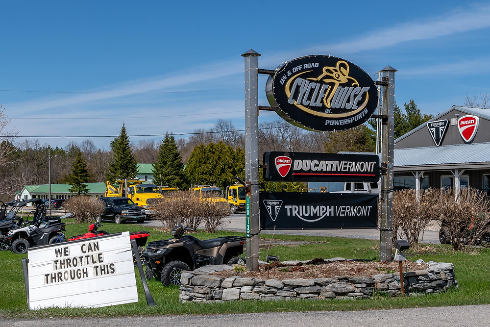 A sign outside Cyclewise Ducati-Triumph Vermont urges customers to throttle through