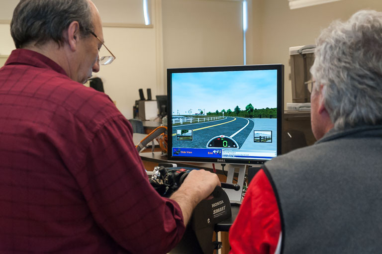 Eddie Krasnow tries the simulator while instructor Bill Mitchell looks on