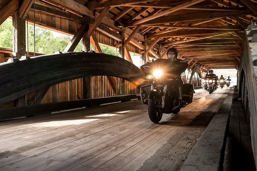 A motorcyclist rides across a covered bridge