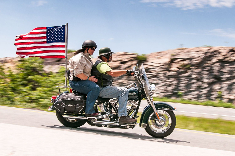 Motorcycle riders riding with an American flag at Vermont Thunder