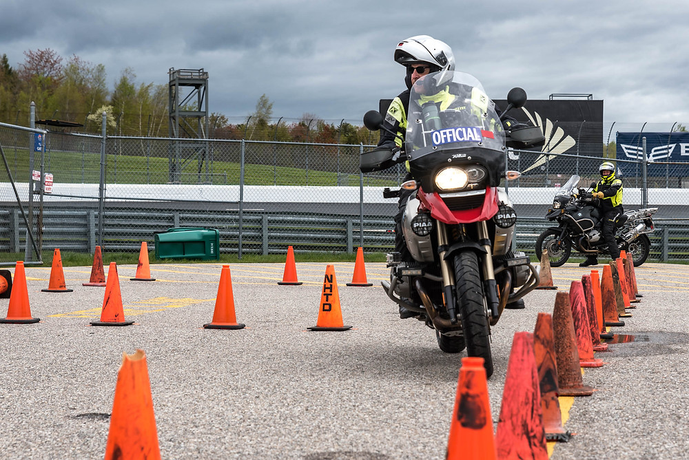 A motorcycle rider navigates through cones during a training class