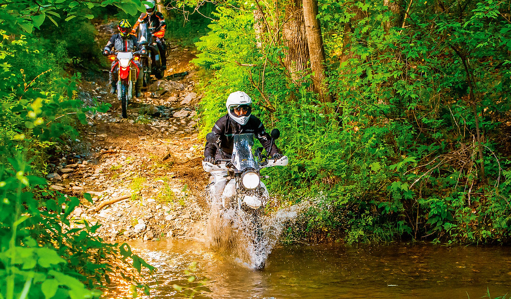 A motorcyclist crossing a river during the DirtDaze Adventure Bike Rally