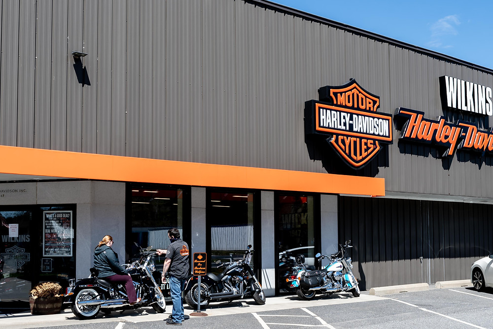 A mask wearing salesman at Wilkins Harley shows a customer a motorcycle