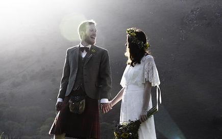 bride in boho dress and groom in kilt outside in snowdonia national park