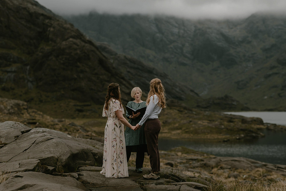 Two brides holding hands at their elopement ceremony at Loch Coruisk, Isle of Skye