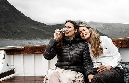 Two women drinking prosecco on a boat after elopement ceremony