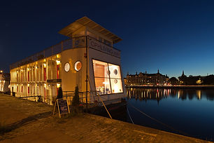 """There is nowhere else quite like this in Copenhagen – and you won't find anything closer to the water. A floating 12-bedroom hotel converted from an old German barge, it's permanently moored in the city centre and makes an unusual, relaxing place to stay. Just being a boat earns plenty of points on the character front, and the Danish eye for design is also much in evidence, with simple, contemporary styling, natural woods and splashes of colour from original paintings and red accessories. There are Arne Jacobsen desk chairs and Le Klint lamps in the bedrooms, and the double-height reception/communal area features an eye-catching light fitting made from a cluster of big bare bulbs on long red wires. The rooms, spread over two decks, are compact but clean-lined and uncluttered, with hardwood floors and a nifty streamlined storage unit that also houses the TV. Beds are comfortable, bathrooms simple but functional, and windows all along one wall look over the water, with reflective glass that prevents passing kayakers from seeing in."