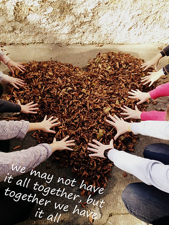 """Photo of many hands reaching onto a heart made from Autumn leaves with the words """"We may not have it all together, but together we have it all."""""""
