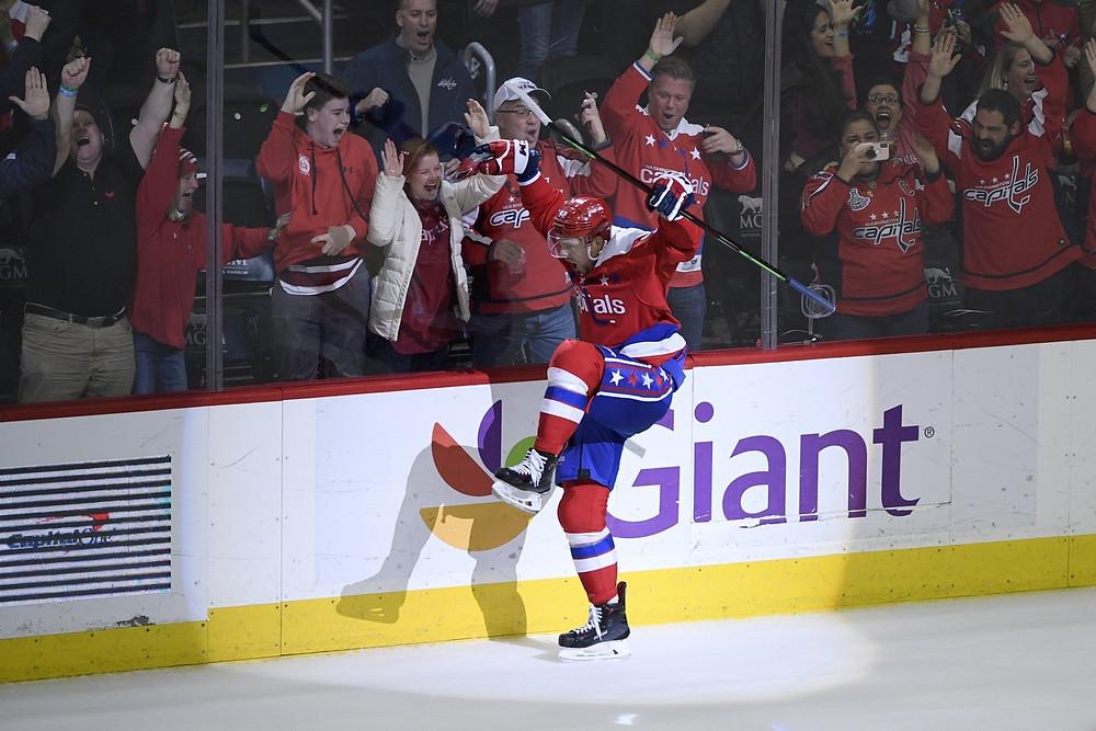 patinador de hockey no gelo comemorando junto com a torcida que está do utro lado do vidro
