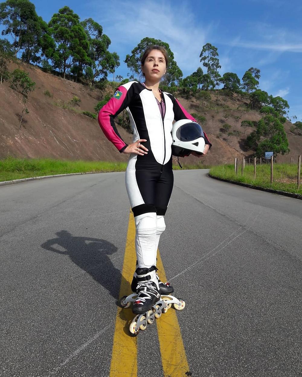 Atleta Camila Cavalheiro com macacão em couro branco e rosa, segurando seu capacete de downhill na mão.