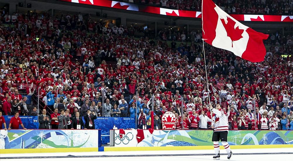 Atleta de patinação no gelo do time do canadá, levantando a bandeira de seu país após a vitória do time, e  muitos torcedores na arquibancada comemorando juntos