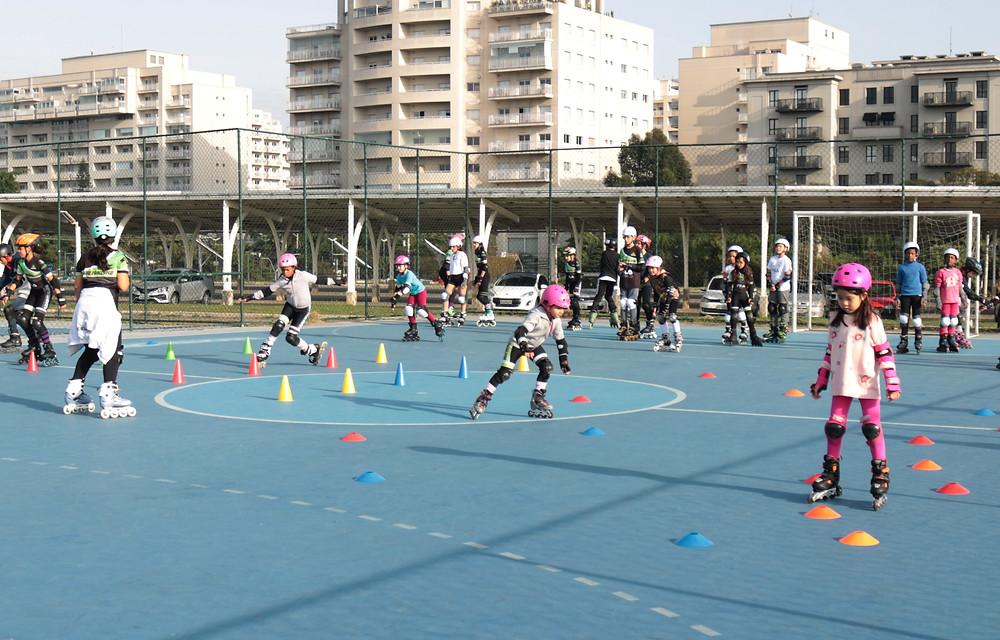 várias crianças patinando em uma quadra de piso azul, ao fundo alguns prédios, na quadra há alguns cones achatados e outros compridos onde as crianças estão realizando alguns exercícios no treino de patinação.