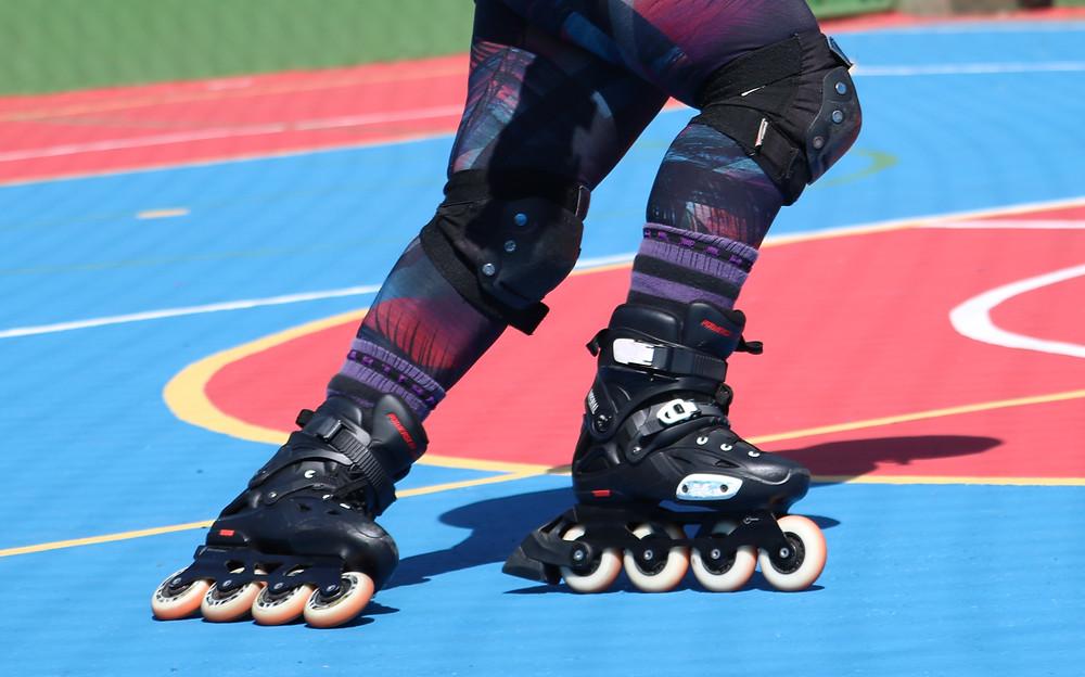 foto de uma perna de um patinador com patins com freio realizando o crossover (curva cruzando os pés) em uma quadra poliesportiva