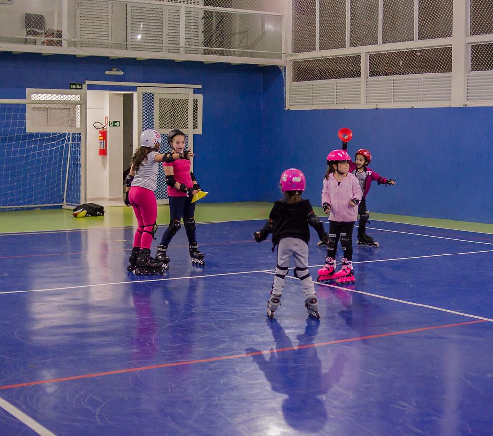 Cinco crianças patinando e se divertindo em uma quadra de piso azul.