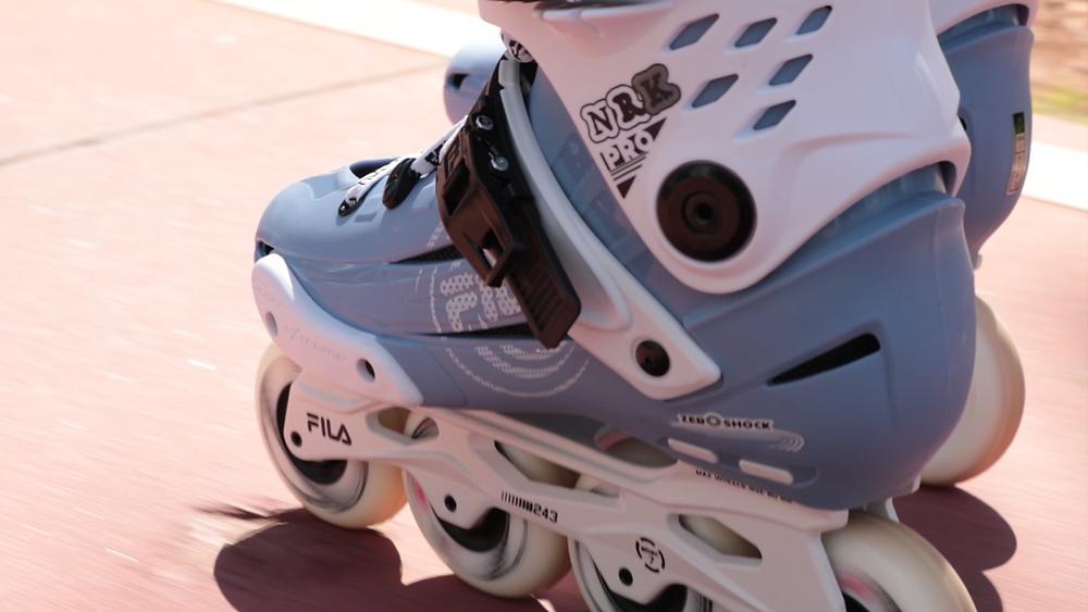 Patins NRK Pro Lightblue, é um patins com rodas e base brancas, bota azul clara e presilhas pretas. Foto do patins rodando em uma ciclofaixa.