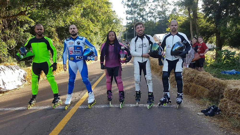 Foto de 5 competidores de inline downhill, da esquerda para a direita: Charles de macacão verde limão, Anderson dantas de macacão azul e branco, Ariele de macacão roxo e preto, Cristiano de macacão branco e preto, e Anderson Barão também de macacão branco e preto.